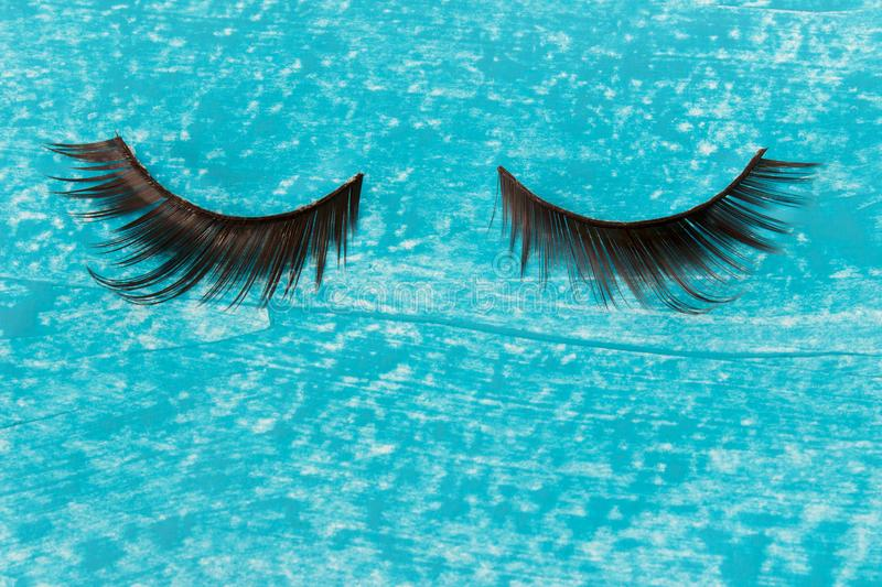 Glamorous artificial female decorative sticky eye lashes. With curly hairs bristles on textured blue acrylic paint background. Photo with copy blank space stock image