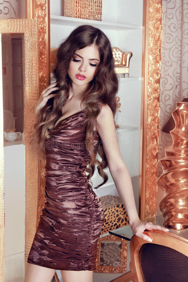 Glamorous beautiful girl model with long wavy hair. Female posing over luxury furniture, beauty and fashion concept. royalty free stock photos