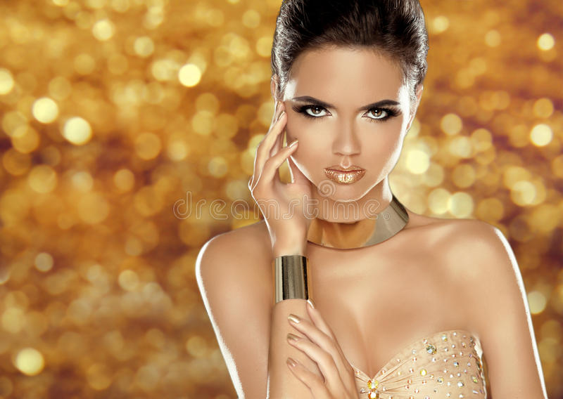 Glamorous beauty fashion girl portrait. Beautiful Young Woman over golden holiday bokeh lights background. Luxury jewelry, makeup. Accessories stock image
