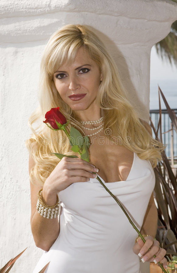 Glamorous Blond woman Holding a Red Rose. In a White Dress royalty free stock image