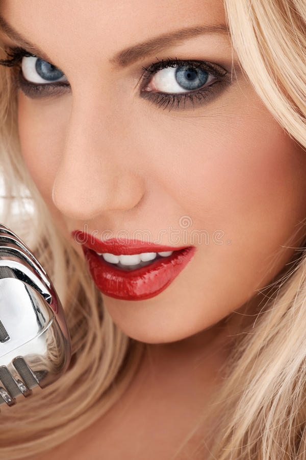Glamorous blonde vocalist or diva. Closeup cropped headshot of a glamorous beautiful blonde vocalist or diva with shiny red lipstick singing at the microphone stock images