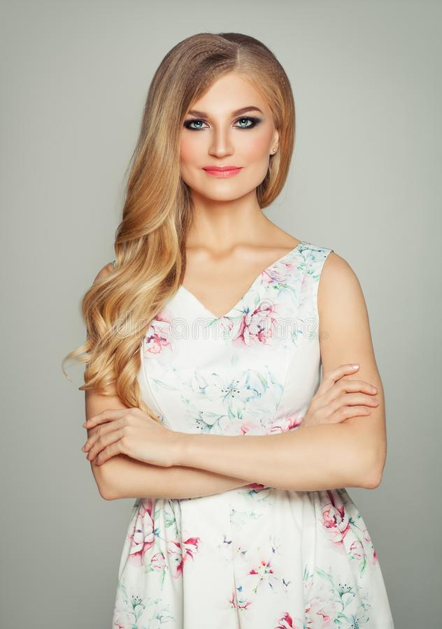 Glamorous blonde woman with crossed arms. Girl with long healthy curly hair and makeup, fashion portrait stock photos