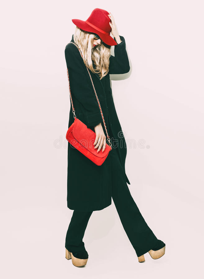 Glamorous fashion blond girl in classic black coat and red hat. royalty free stock photos