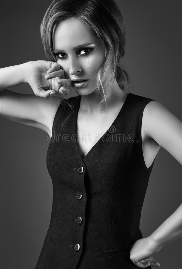 Seductive blonde girl in pants and a man`s waistcoat royalty free stock photos