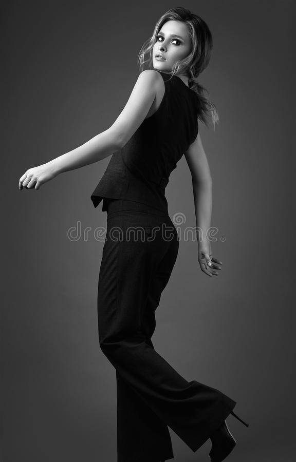 Seductive blonde girl in pants and a man`s waistcoat stock images