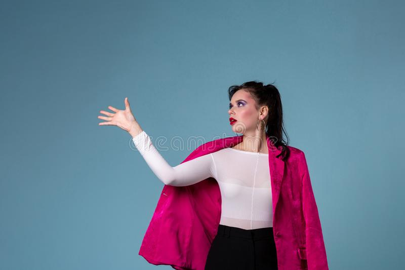 Glamorous girl with colorful makeup wearing ping jacket cathes something royalty free stock photography