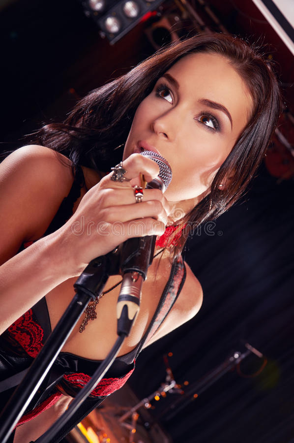 Glamorous girl singing on the stage stock images