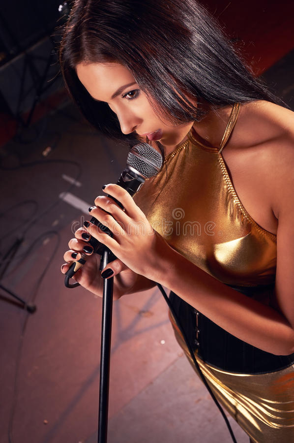 Glamorous girl singing on the stage royalty free stock image