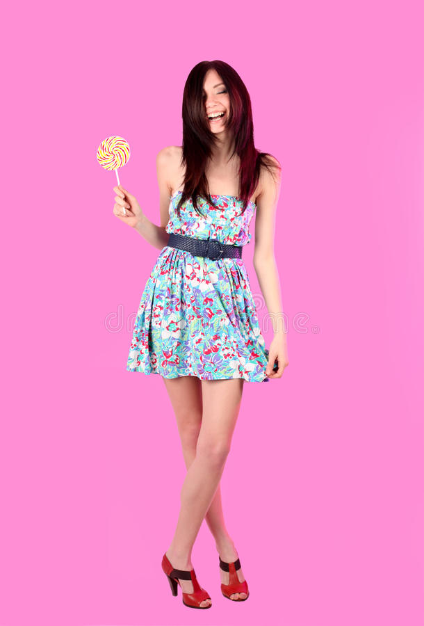 Glamorous girl wearing colorful dress with lollipo. Glamorous cheerful girl wearing colorful dress with lollipop over pink background stock photo