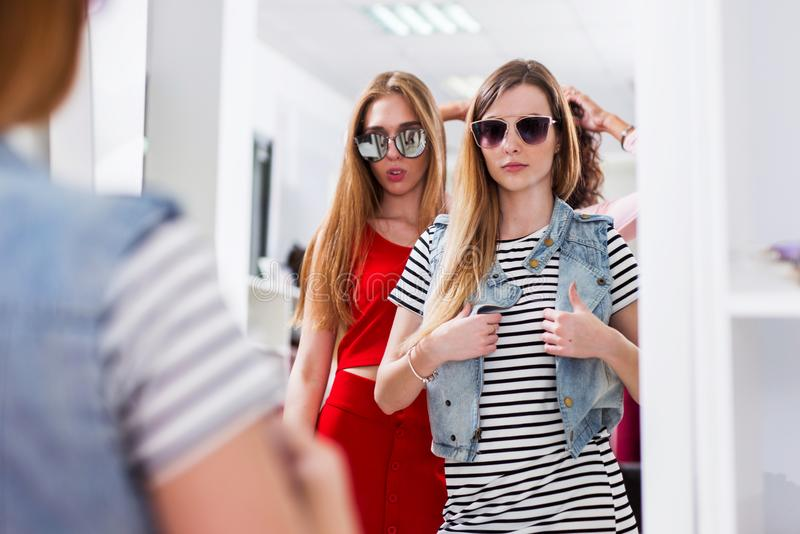 Glamorous girls trying on sunglasses posing in front of the mirror in fashion boutique.  stock image