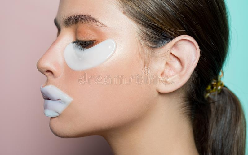 Glamorous healthy model with beautiful face using patches for eyes and lip. Spa skin procedure for health and beauty royalty free stock image