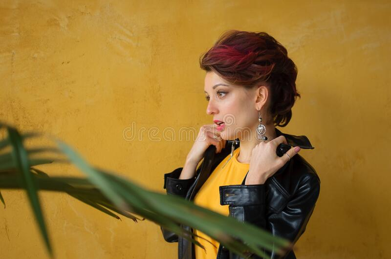 Glamorous lady in punk rock style party clothes with dark pink hair in casual dress, black leather jacket, and long. Earrings on yellow background royalty free stock image