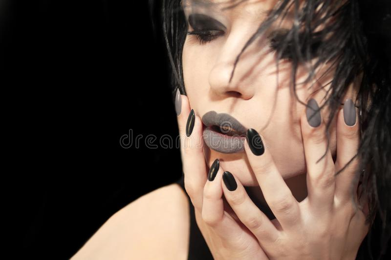 Glamorous matte black gray makeup, and manicures on a sharply oval-shaped nails with feathers of a model on a grey background. royalty free stock photography