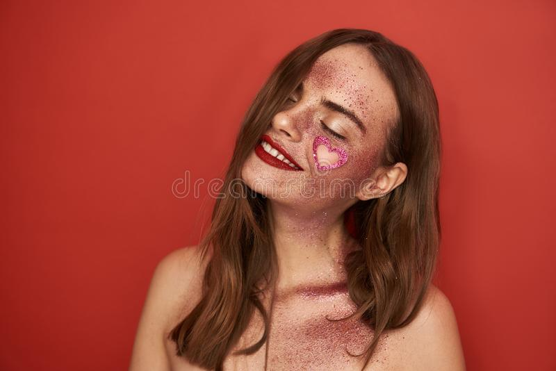 Happy young girl with closed eyes and creative makeup on red background stock photography