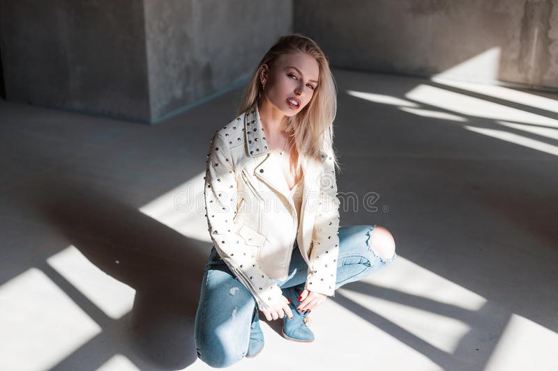 Glamorous modern attractive blond woman in vintage green cowboy boots in a summer leather jacket in ripped jeans sits in a room royalty free stock photo