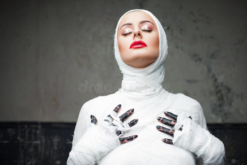Glamorous mummy. Portrait of a young beautiful woman in bandages all over her body. Halloween or plastic surgery concept stock photo