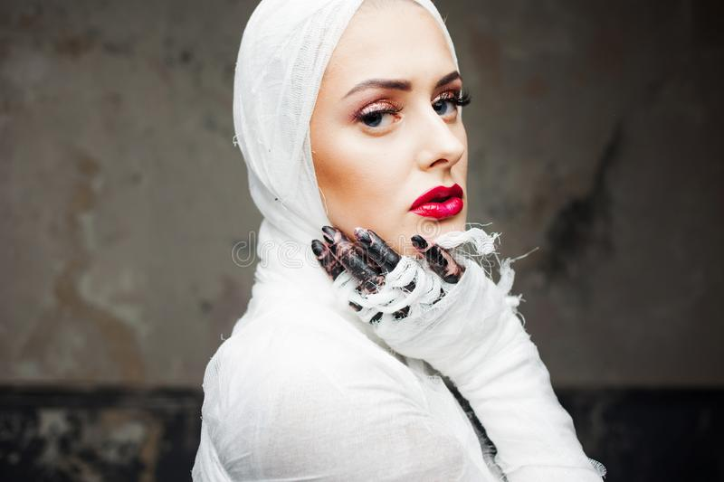 Glamorous mummy. Portrait of a young beautiful woman in bandages all over her body. Halloween or plastic surgery concept royalty free stock photo