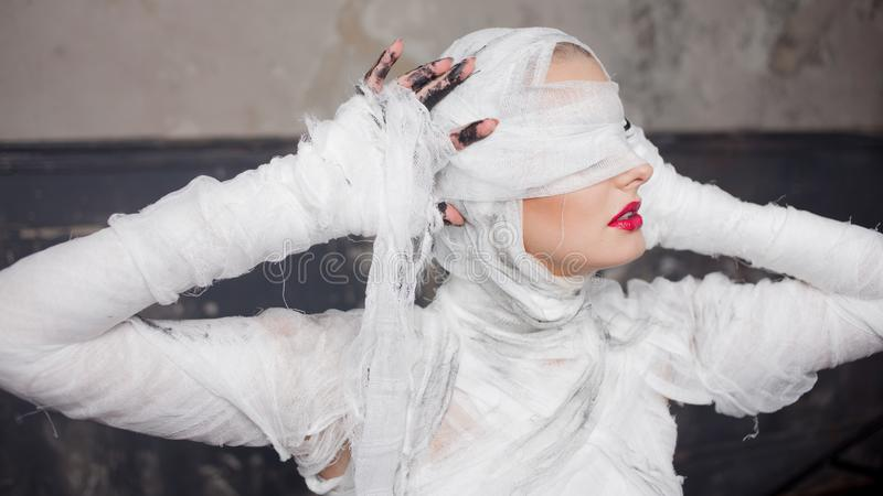 Glamorous mummy. Portrait of a young beautiful woman in bandages all over her body. Halloween or plastic surgery concept stock images