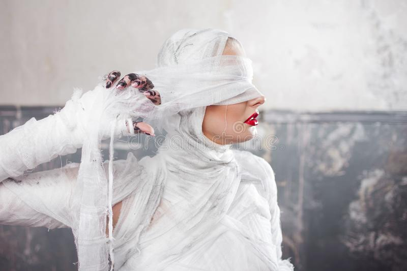 Glamorous mummy. Portrait of a young beautiful woman in bandages all over her body. Halloween or plastic surgery concept stock photography