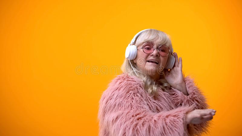 Glamorous old woman in headphones listening music, pretending to be DJ, hobby stock image