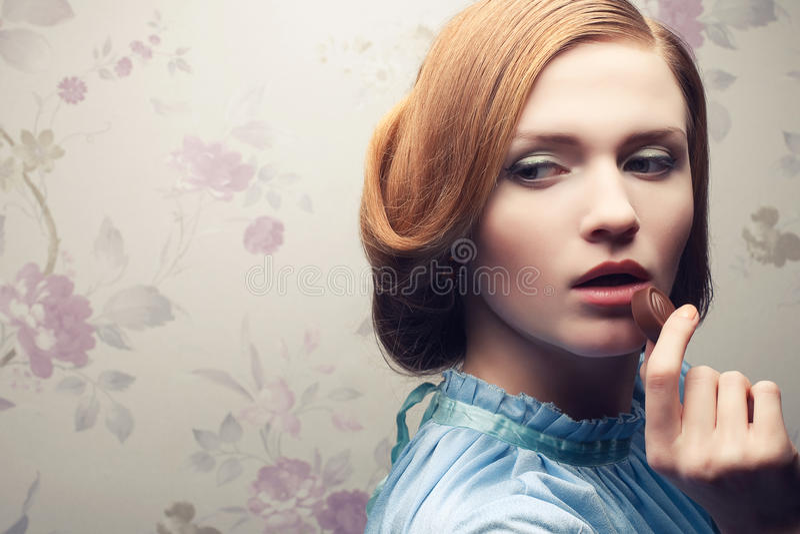 Glamorous red-haired (ginger) girl eating bonbon royalty free stock photography