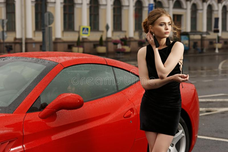 woman against red sport car stock image
