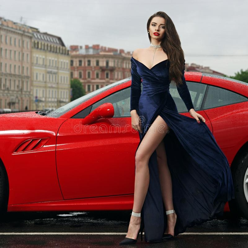 woman against red sport car royalty free stock photography