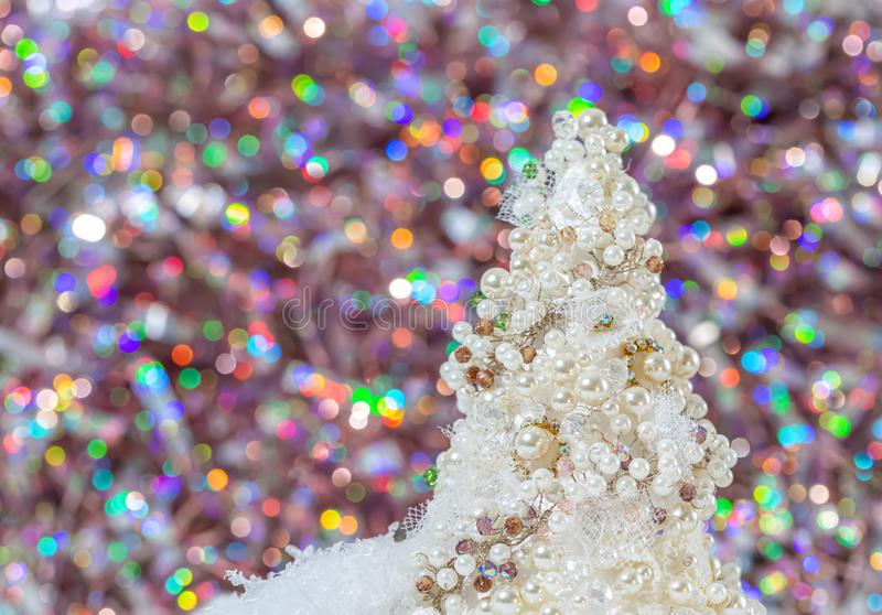 Christmas tree with pearls and beads on the snow next to beautiful blurred bokeh background and glowing garland.Copy space.Closeup. Glamorous white artificial royalty free stock photography