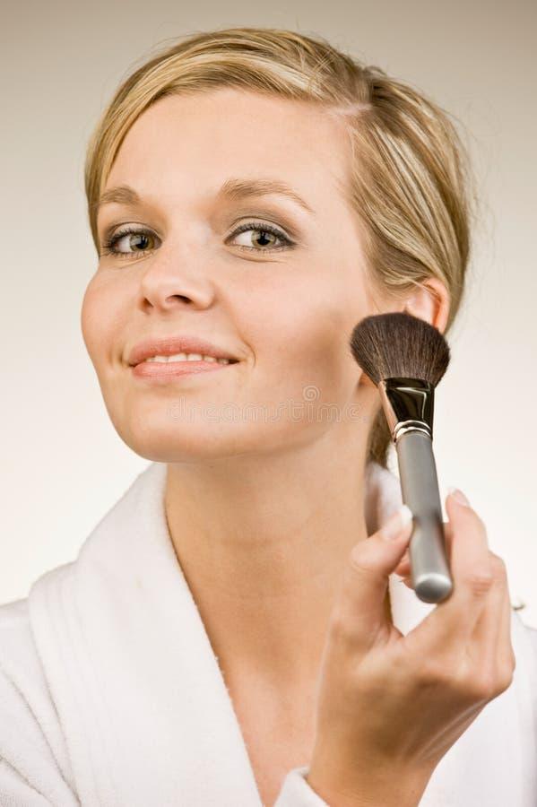 Glamorous woman applying blush with makeup brush royalty free stock images