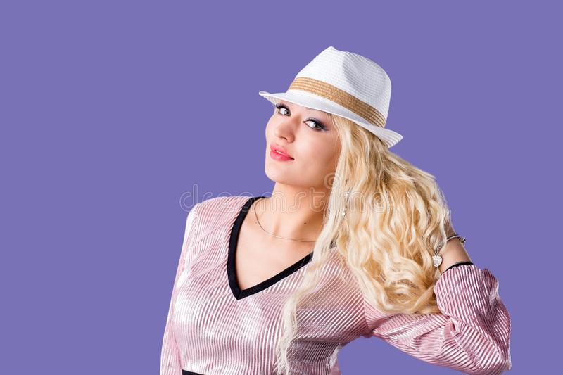 Beautiful young woman in sun hat on purple background royalty free stock photos