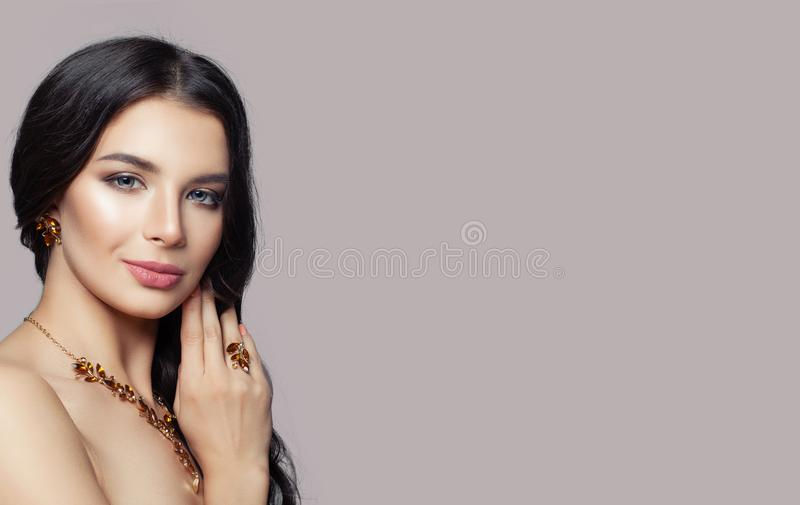 Glamorous woman wearing gold necklace, ring and earrings with amber on pink background with copy space.  royalty free stock photography