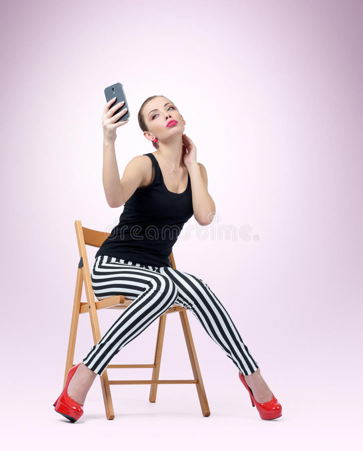 Glamorous young woman sitting on chair making selfie. Background stock image
