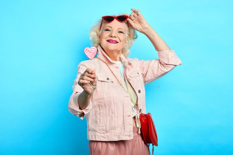 Glamour awesome blonde senior lady taking off sunglasses, while eating lollipop royalty free stock photo
