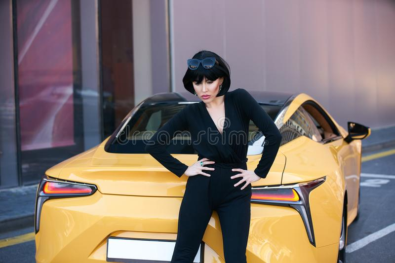 Glamour brunette babe standing near luxury sport car royalty free stock photography