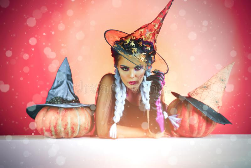 Glamour fashion halloween vampire lady with witch halloween hat. Woman in witches hat and costume pointing hand - stock images