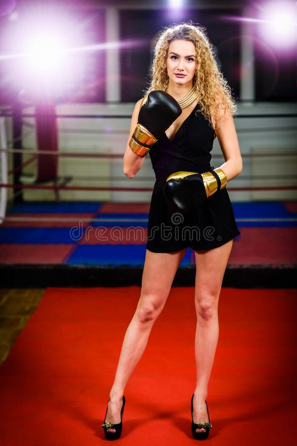 Glamour fashion model woman with boxing gloves in sports gym. Strong, active, independent female in high heels on the red carpet is wearing golden kick boxing stock images