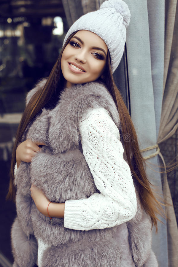 Glamour girl with dark straight hair wears luxurious fur coat and knitted hat. Fashion street outfit, beautiful glamour girl with dark straight hair wears royalty free stock photography