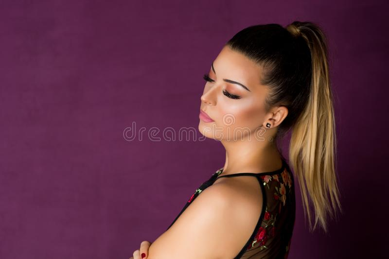 Glamour Girl with make up and silk eyelashes looking down and posing on purple background. Glamour young Girl with silk eyelashes looking down and posing on stock images