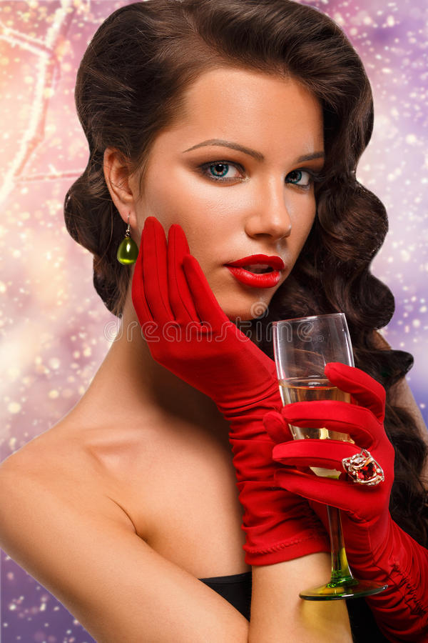 Glamour girl in red gloves holding a glass of champagne. drinking champagne. Beauty woman with perfect fashion makeup. royalty free stock photography