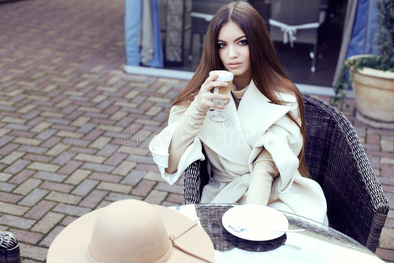 Glamour girl wears luxurious beige coat drinking coffee. Fashion street outfit, beautiful glamour girl with dark straight hair wears luxurious beige coat with royalty free stock photography