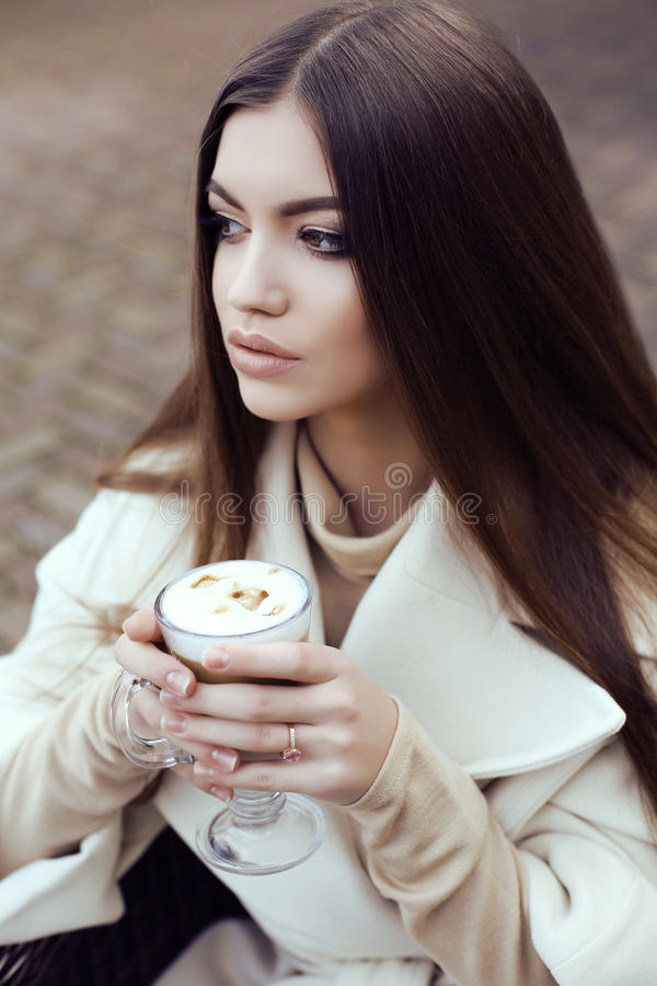 Glamour girl wears luxurious beige coat drinking coffee. Fashion street outfit, beautiful glamour girl with dark straight hair wears luxurious beige coat stock images