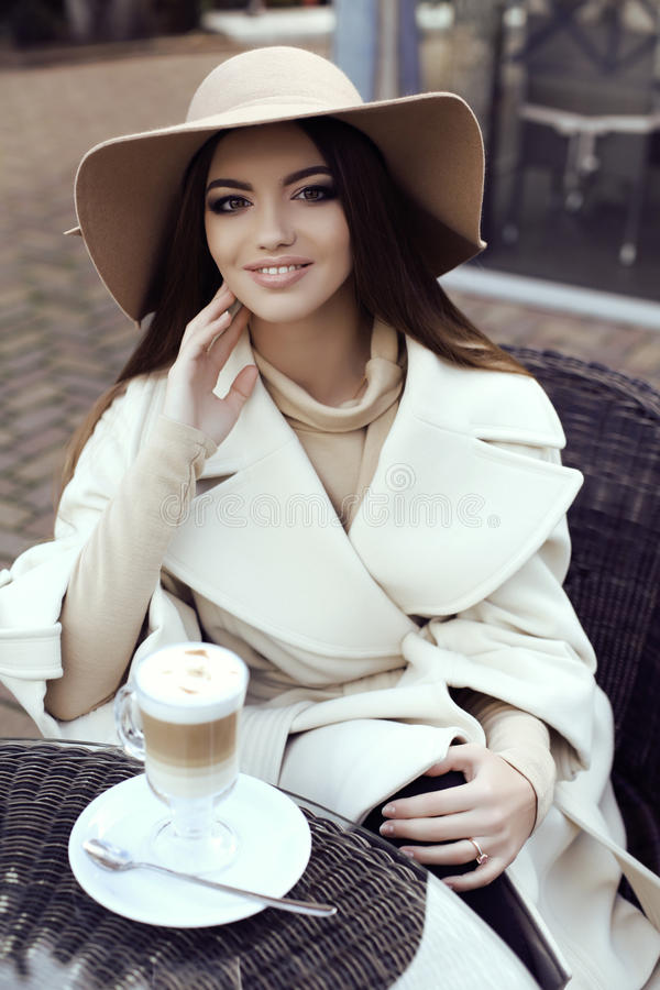 Glamour girl wears luxurious beige coat with elegant hat. Fashion street outfit, beautiful glamour girl with dark straight hair wears luxurious beige coat with royalty free stock image