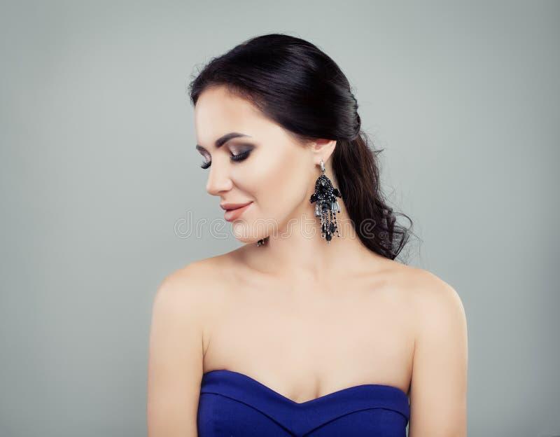 Glamour jewelry model. Brunette woman with earrings portrait stock image