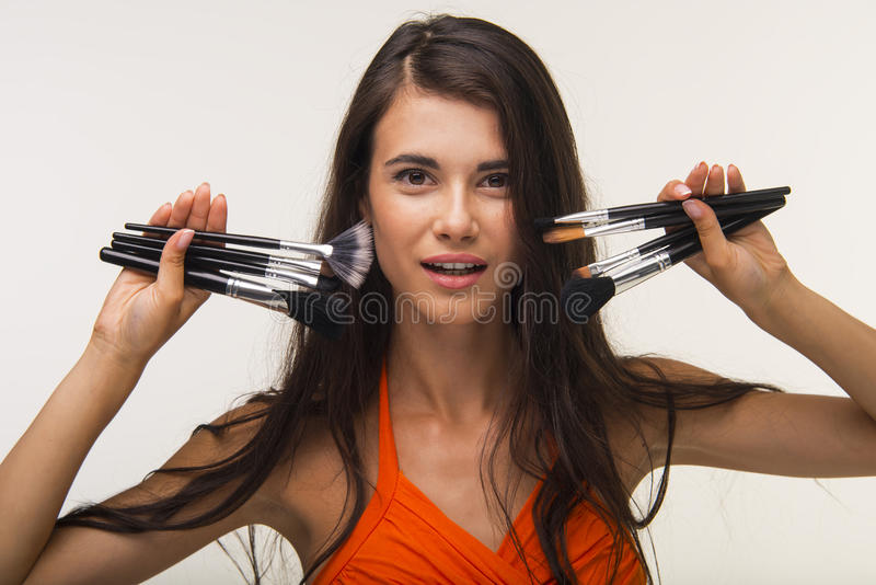 Glamour lady is showing cosmetic brushes. royalty free stock photo