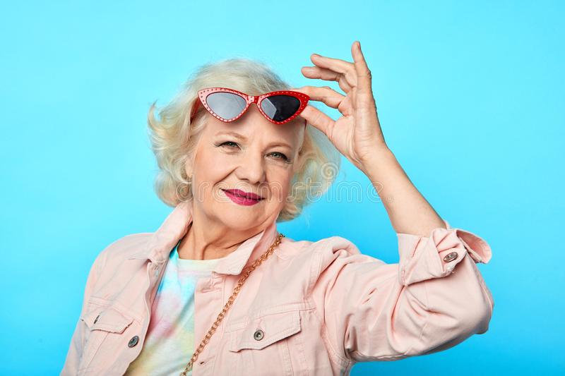 Glamour old woman taking off, putting on sunglasses royalty free stock photography