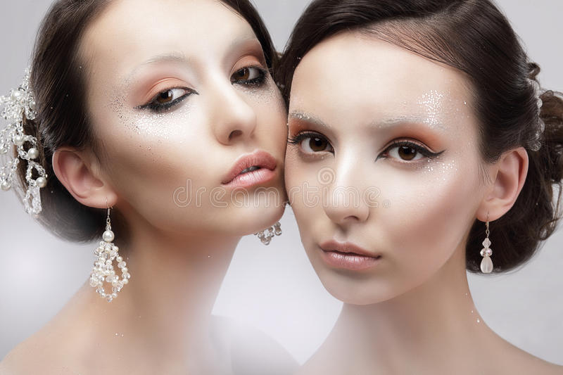 Glamour. Portrait of Two Women with Shiny Glossy Makeup royalty free stock images