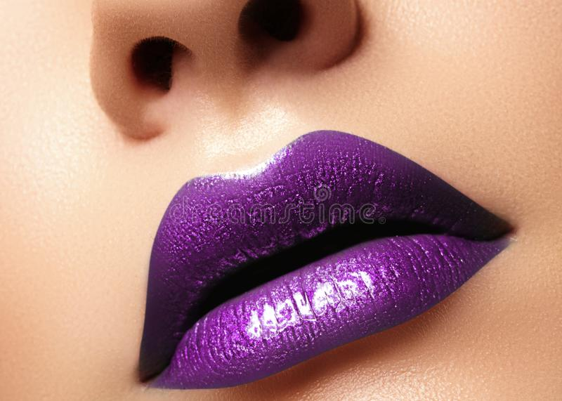Glamour purple Gloss Lips with sensuality gesture. style, closeup macro shot female Lip Make-up. Sensuality mouth royalty free stock photos