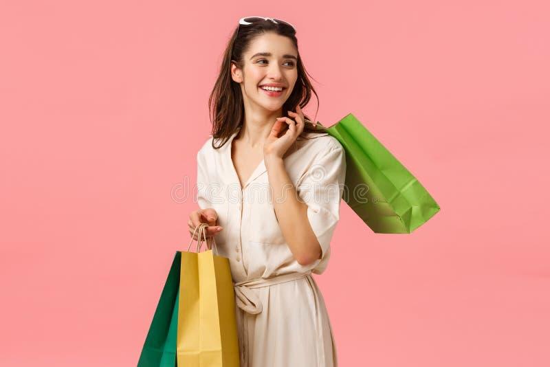Glamour relaxado e descuidada, garota feminina fofa em vestidos segurando bolsas e virando à direita com linda felicidade fotos de stock royalty free