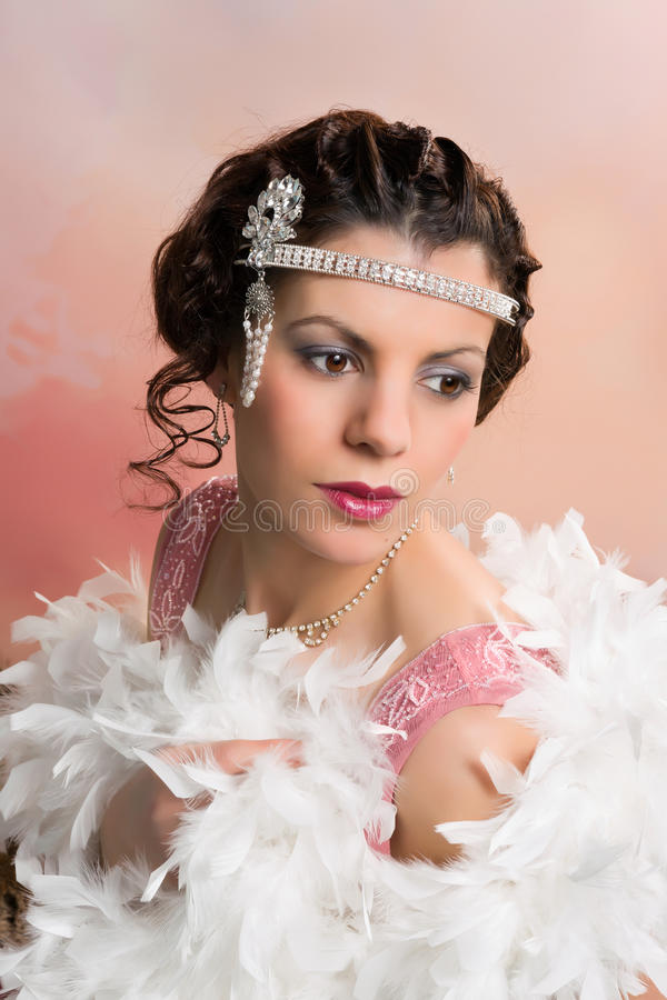 Glamour 1920s woman. Beautiful vintage 1920s lady wearing a headband and white feather boa stock images
