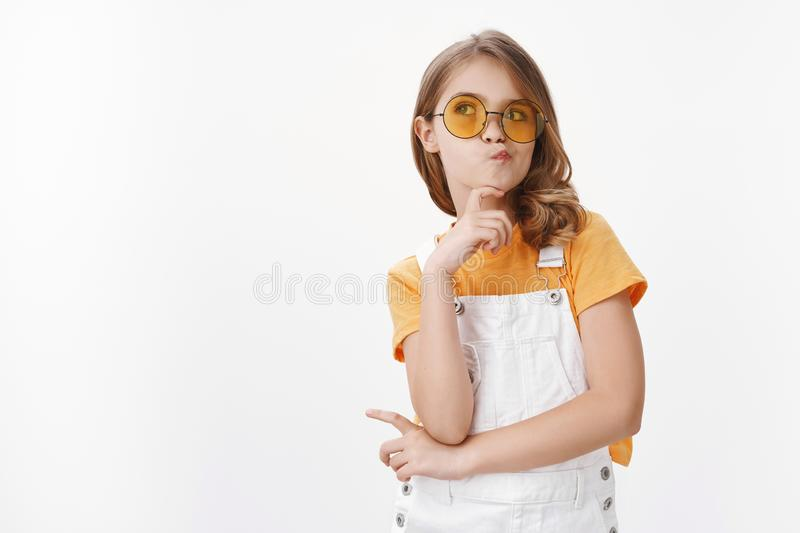 Glamour sassy pretty little fashionable girl with blond hair, wear yellow sunglasses and overalls, pouting smirk royalty free stock photo